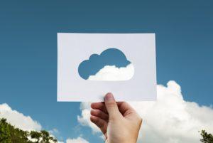 雲の形に切り抜いた紙を空に掲げている